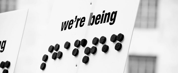 """Black and white close up photo of a 2011 banner, """"We're being Shafted"""" by the government (shafted as braille letters)"""