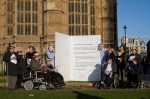 Supporters of the Hardest Hit Campaign stand with our giant Christmas Card outside Parliament, the card is opened revealing messages and signatures inside