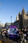 Supporters of the Hardest Hit Campaign and our delegation stand with our giant Christmas Card outside Parliament, Big Ben stands in the background of this photo