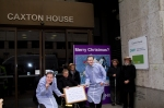 2 members of the Hardest Hit team dressed in night gowns, one wearing a Nick Clegg mask and one wearing a David Cameron mask stand with the Hardest Hit delegation outside the DWP offices at Caxton House