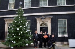 The Hardest Hit Delegation stand next to the large Christmas tree outside Downing St with the box containing the full list of Hardest Hit Christmas Card Signatures
